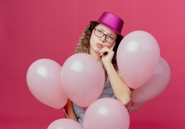 Kijkend naar kant denkende jong meisje met bril en roze hoed met ballonnen en hand op wang geïsoleerd op roze achtergrond te zetten