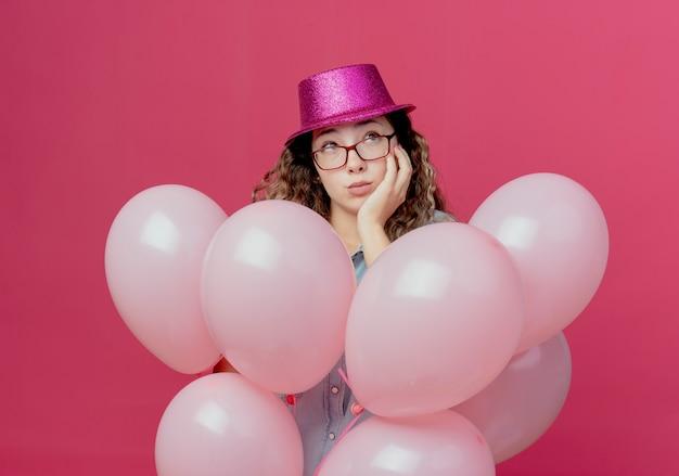 Kijkend naar kant denkende jong meisje met bril en roze hoed staande onder ballonnen en hand zetten wang geïsoleerd op roze achtergrond