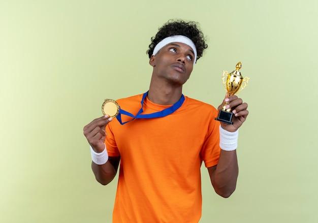 Kijkend naar kant denkende jonge afro-amerikaanse sportieve man met hoofdband en polsbandje en medaille houden beker geïsoleerd op groene achtergrond
