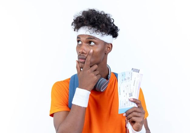 Kijkend naar kant denkende jonge afro-amerikaanse sportieve man met hoofdband en polsbandje kaartjes houden en hand op wang zetten geïsoleerd op witte achtergrond