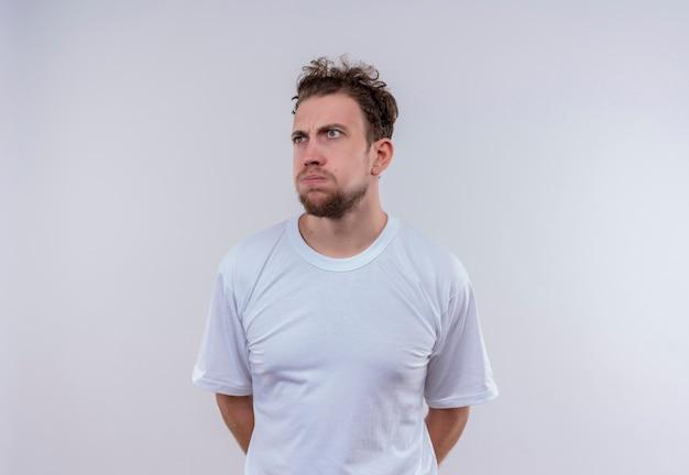 Kijkend naar kant denkende jonge kerel met een wit t-shirt legde zijn hand op de rug op geïsoleerde witte achtergrond