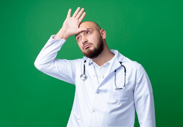 Kijkend naar kant denkende jonge mannelijke arts die medische mantel en stethoscoop draagt die hand op hoofd zet dat op groene achtergrond wordt geïsoleerd