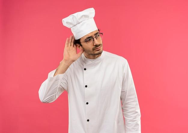 Kijkend naar kant denkende jonge mannelijke kok die eenvormige chef-kok en glazen draagt die luistergebaar tonen