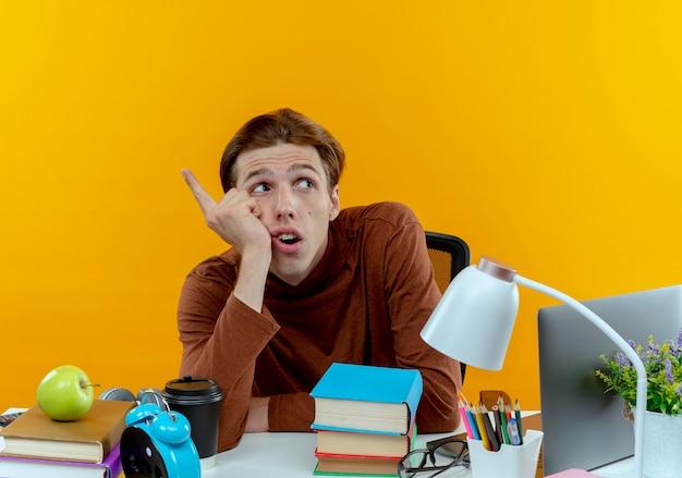 Kijkend naar kant denkende jonge student jongen zit aan bureau met school tools punten aan de zijkant