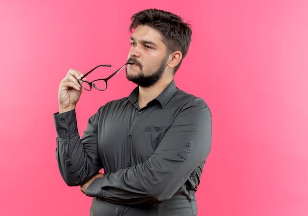 Kijkend naar kant denkende jonge zakenman aanraken mond met glazen geïsoleerd op roze muur