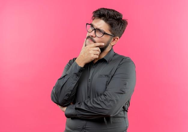 Kijkend naar kant denkende jonge zakenman die een bril draagt die hand onder de kin zet die op roze muur wordt geïsoleerd