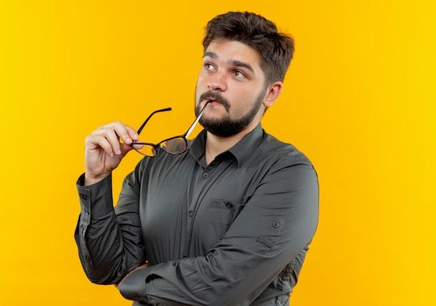 Kijkend naar kant denkende jonge zakenman glazen op mond zetten geïsoleerd op gele achtergrond