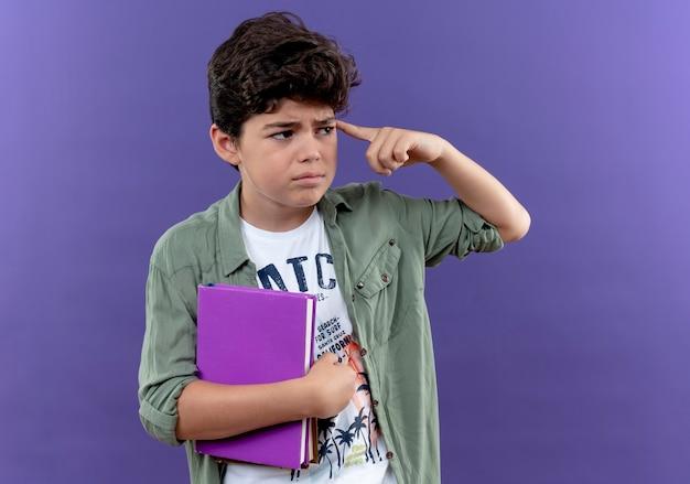 Kijkend naar kant denkende kleine schooljongen met boek en vinger op het hoofd te zetten