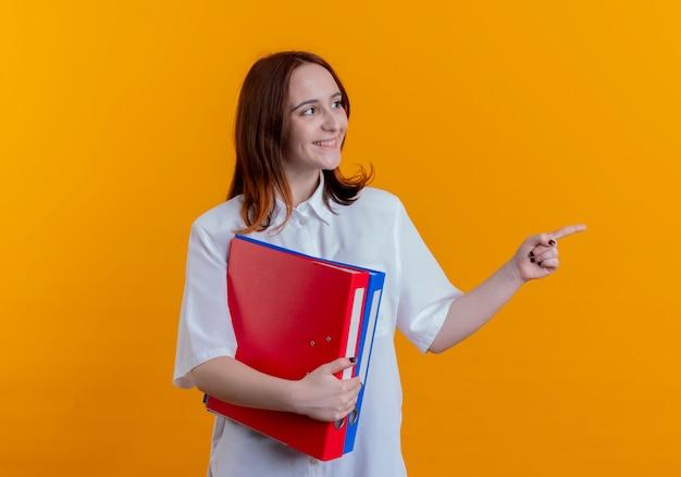 Kijkend naar kant glimlachend jong roodharig meisje met mappen en punten aan de zijkant geïsoleerd op gele achtergrond met kopie ruimte