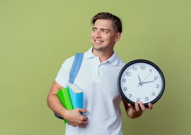 Kijkend naar kant glimlachende jonge knappe mannelijke student die rugtas draagt met boeken en muurklok die op olijfgroene achtergrond wordt geïsoleerd