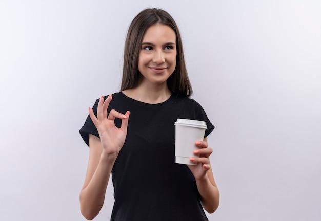 Kijkend naar kant jong kaukasisch meisje die zwarte t-shirt dragen die kop van koffie houden die ok gebaar op geïsoleerde witte achtergrond tonen
