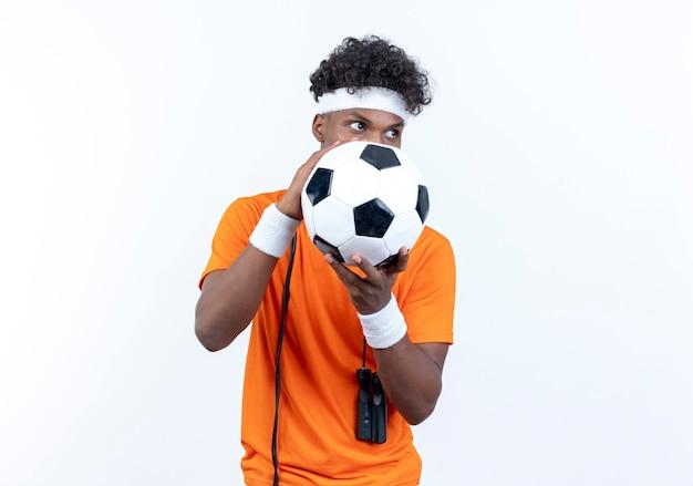 Kijkend naar kant jonge afro-amerikaanse sportieve man met hoofdband en polsband bedekt gezicht met bal met springtouw op schouder