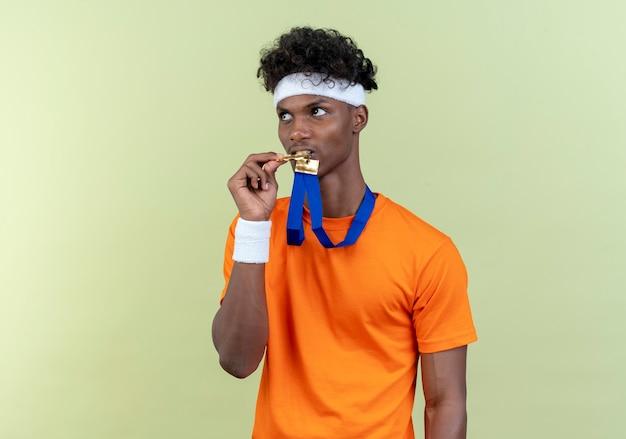 Kijkend naar kant jonge afro-amerikaanse sportieve man met hoofdband en polsbandje houden en bijt medaille op nek geïsoleerd op groene achtergrond