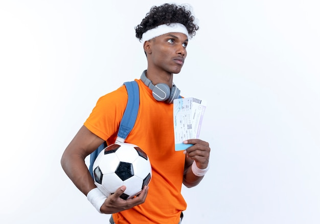 Kijkend naar kant jonge afro-amerikaanse sportieve man met hoofdband en polsbandje met bal en kaartjes geïsoleerd op een witte achtergrond