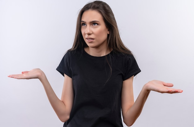 Kijkend naar kant jonge blanke meisje met zwarte t-shirt spreidt handen op geïsoleerde witte achtergrond