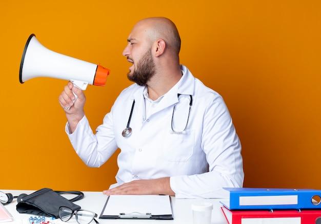 Kijkend naar kant jonge kale mannelijke arts die medische gewaad en stethoscoop draagt ?? die aan het bureau zit met medische hulpmiddelen spreekt op luidspreker geïsoleerd op een oranje achtergrond