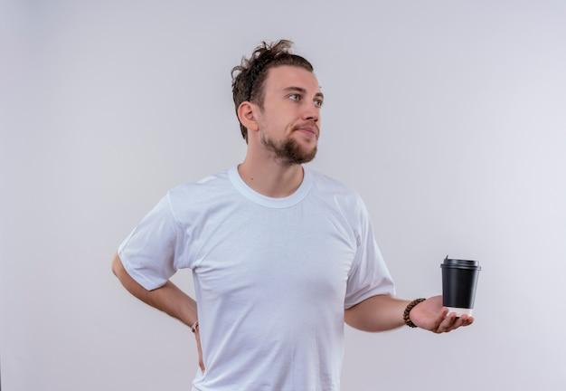 Kijkend naar kant jonge kerel die een wit t-shirt draagt en een kopje koffie houdt, legde zijn hand op de heup op afgelegen witte achtergrond