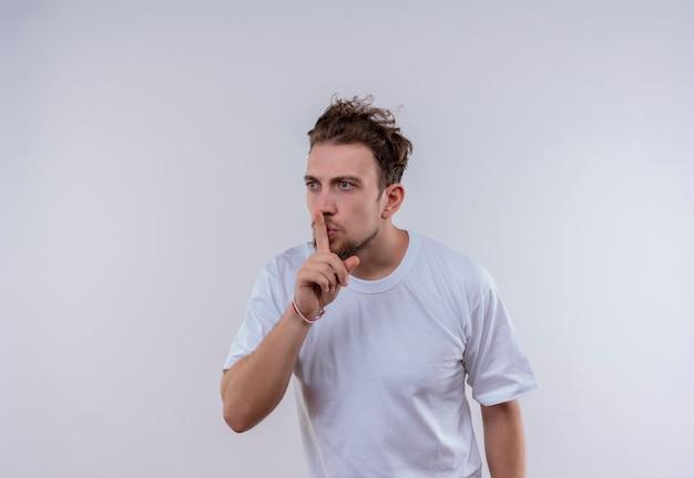 Kijkend naar kant jonge kerel die wit t-shirt draagt dat stilte gebaar op geïsoleerde witte achtergrond toont