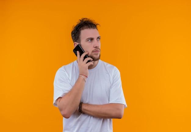 Kijkend naar kant jonge kerel met een wit t-shirt spreekt aan de telefoon en kruising hand op geïsoleerde oranje achtergrond