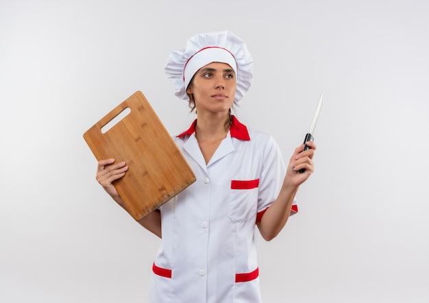 Kijkend naar kant jonge vrouwelijke kok dragen chef-kok uniforme bedrijf snijplank en mes op geïsoleerde witte muur met kopie ruimte