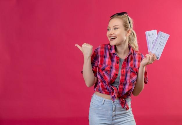 Kijkend naar kant jonge vrouwelijke reiziger die rood shirt in glazen draagt die kaartjes op geïsoleerde roze muur houdt