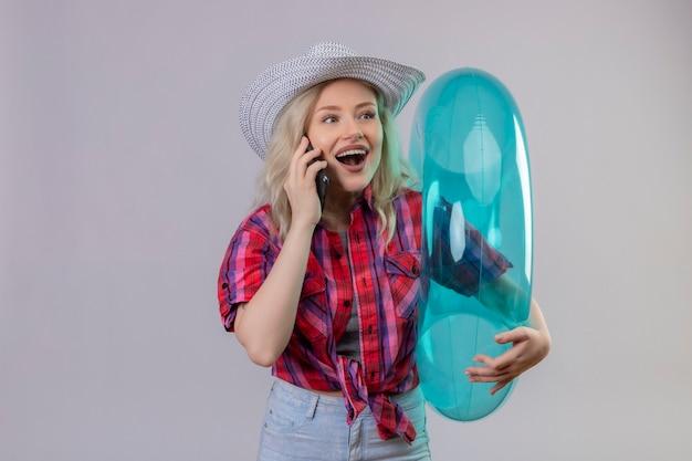 Kijkend naar kant jonge vrouwelijke reiziger draagt rood shirt in hoed met opblaasbare ring spreekt aan de telefoon op geïsoleerde witte muur