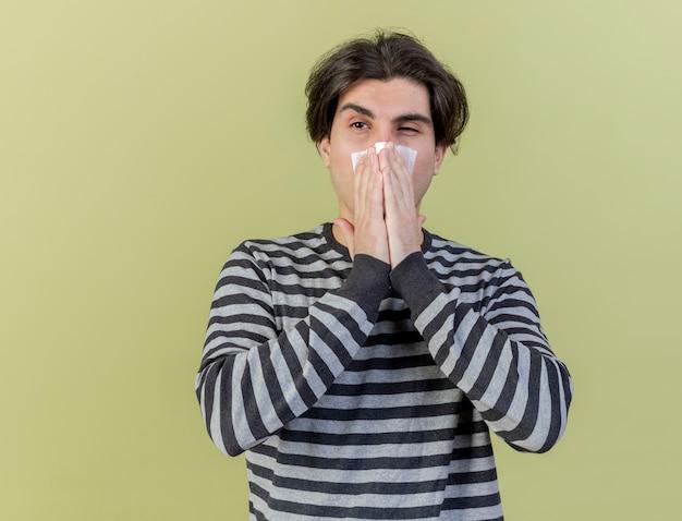 Kijkend naar kant jonge zieke man afvegende neus met servet geïsoleerd op olijfgroene achtergrond