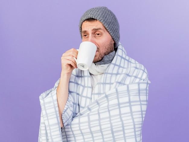 Kijkend naar kant jonge zieke man met winter hoed met sjaal gewikkeld in plaid en het drinken van thee geïsoleerd op paarse achtergrond
