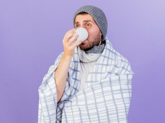 Kijkend naar kant jonge zieke man met winter hoed met sjaal het drinken van thee geïsoleerd op paarse achtergrond