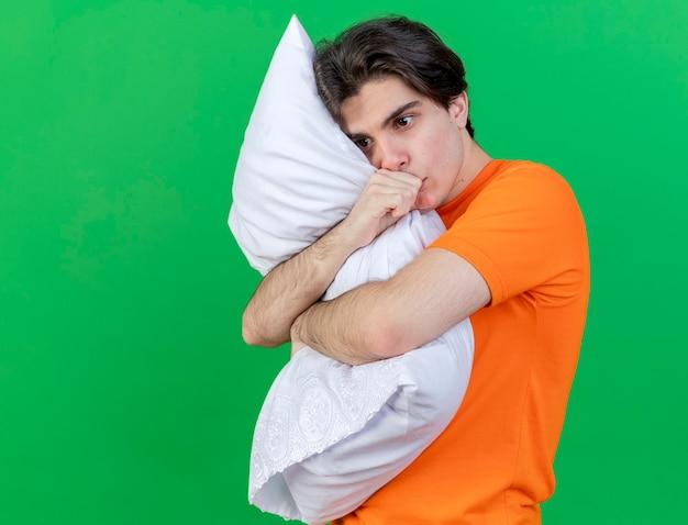 Kijkend naar kant jonge zieke man omhelsde kussen hand op mond zetten geïsoleerd op groene achtergrond