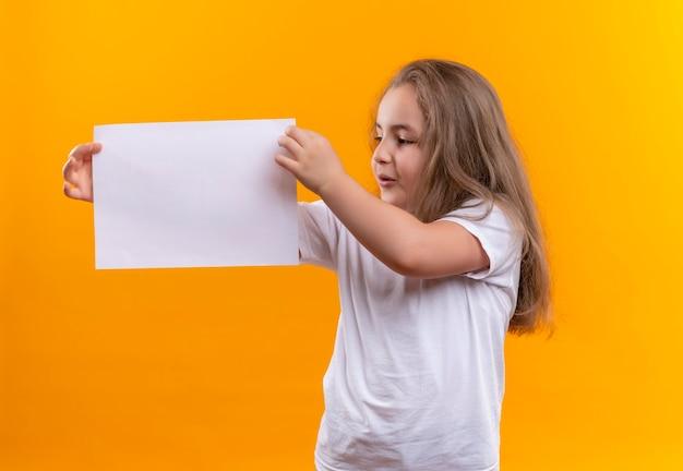 Kijkend naar kant klein schoolmeisje die het witte document van de t-shirtholding op geïsoleerde oranje muur dragen