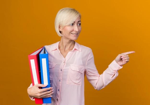 Kijkend naar kant lachende jonge blonde slavische vrouw met mappen en punten aan de zijkant