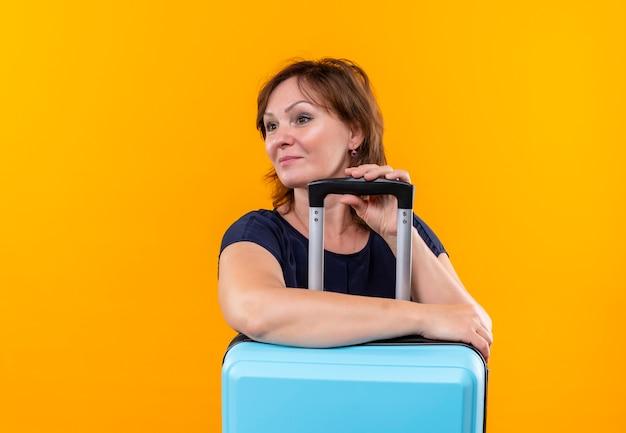 Kijkend naar kant lachende middelbare leeftijd reiziger vrouw handen op koffer op geïsoleerde gele achtergrond