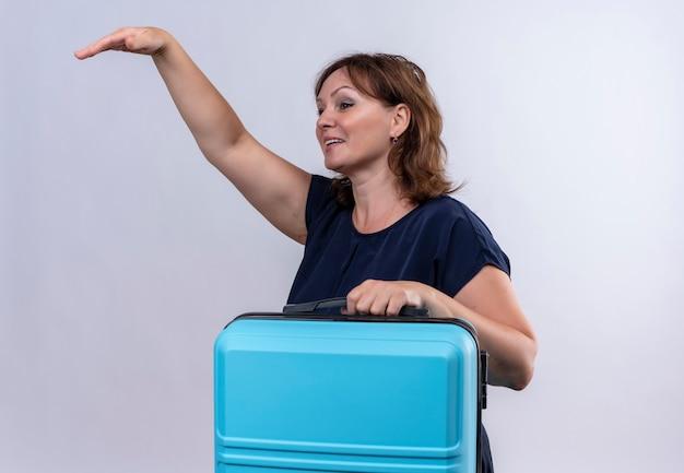 Kijkend naar kant lachende middelbare leeftijd reiziger vrouw met koffer en iemand bellen met de hand op afgelegen witte achtergrond