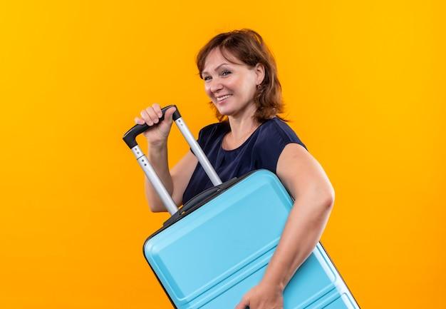 Kijkend naar kant lachende middelbare leeftijd reiziger vrouw met koffer op geïsoleerde gele achtergrond