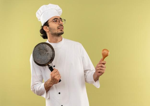 Kijkend naar kant onder de indruk jonge mannelijke kok dragen uniforme chef-kok en glazen met koekenpan en lepel