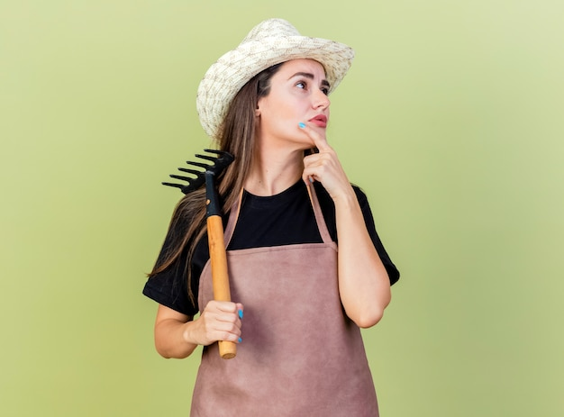 Kijkend naar kant onder de indruk mooi tuinman meisje in uniform dragen tuinieren hoed houden hark