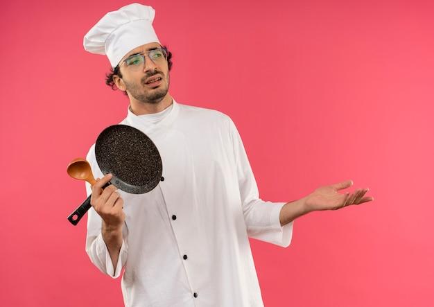 Kijkend naar kant ontevreden jonge mannelijke kok dragen uniform van de chef-kok en glazen houden koekenpan met lepel en uitgespreide hand
