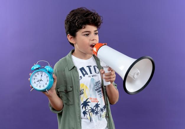 Kijkend naar kant spreekt kleine schooljongen op luidspreker en houdt wekker geïsoleerd op paarse muur