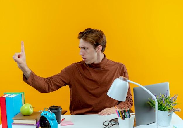 Kijkend naar kant strikte jonge studentenjongen zittend aan een bureau met schoolhulpmiddelen hand aan kant standhouden