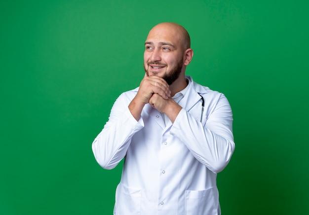 Kijkend naar kant tevreden jonge mannelijke arts dragen medische gewaad en stethoscoop handen onder de kin geïsoleerd op een groene achtergrond