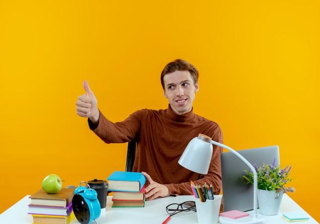 Kijkend naar kant tevreden jonge student jongen zittend aan een bureau met schoolhulpmiddelen zijn duim omhoog