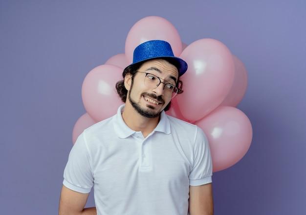 Kijkend naar kant tevreden knappe man met bril en blauwe hoed staande voor ballonnen geïsoleerd op paarse achtergrond