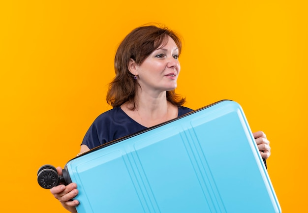 Kijkend naar kant tevreden reiziger vrouw met koffer van middelbare leeftijd op geïsoleerde gele achtergrond