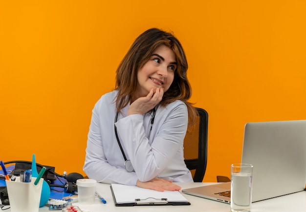 Kijkend naar kant tevreden vrouwelijke arts van middelbare leeftijd dragen medische gewaad met stethoscoop zittend aan een bureau werken op laptop met medische hulpmiddelen hand op kin zetten oranje muur met kopie ruimte
