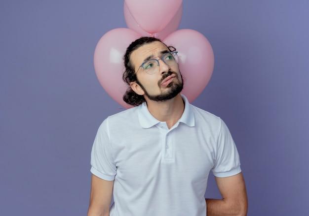 Kijkend naar kant triest knappe man met bril staande voor ballonnen geïsoleerd op paarse achtergrond