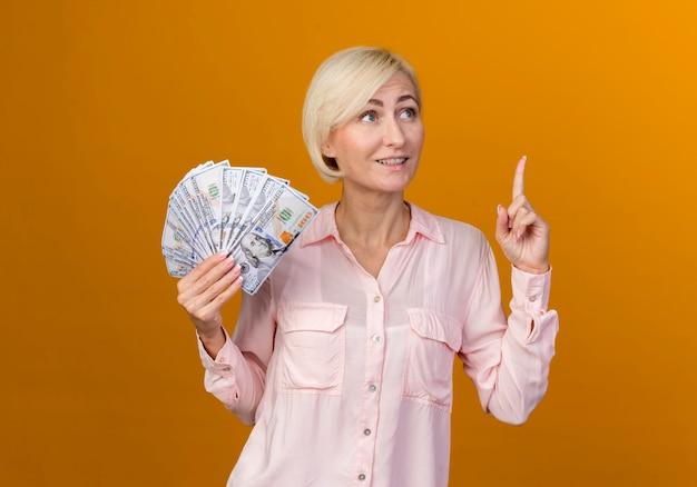 Kijkend naar kant verrast jonge blonde slavische vrouw met contant geld en wijst naar boven