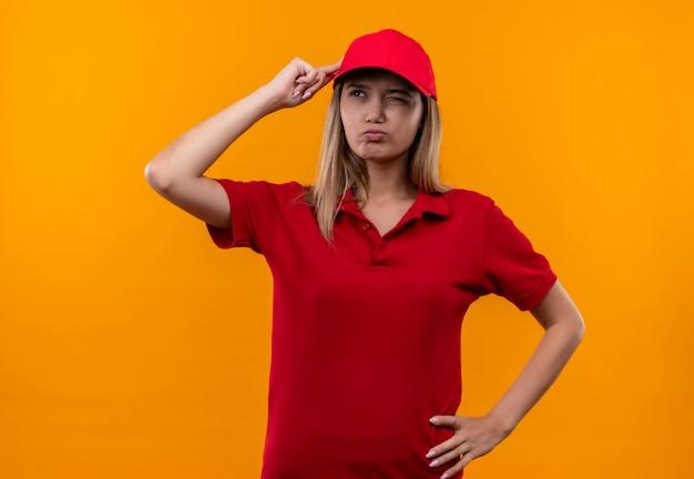 Kijkend naar kant verward jong leveringsmeisje die rood uniform en pet dragen die vinger aan hoofd zetten die op oranje achtergrond wordt geïsoleerd