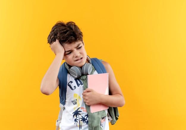Kijkend naar kant verward kleine schooljongen die rugtas en koptelefoon draagt die notitieboekje houdt en hoofd grijpt dat op gele achtergrond wordt geïsoleerd