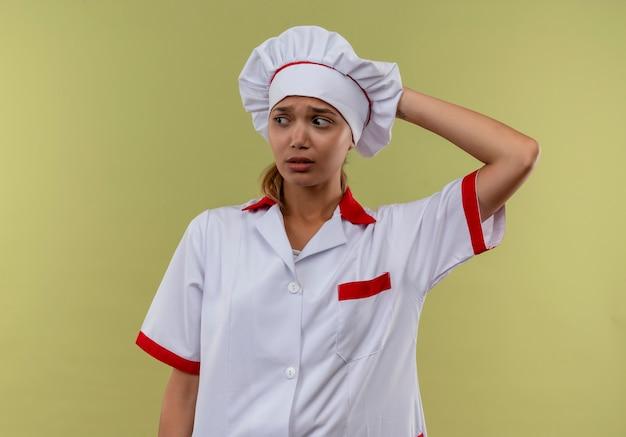 Kijkend naar kant verwarde jonge kok vrouwelijke dragen chef-kok uniform hand op het hoofd zetten op geïsoleerde groene muur met kopie ruimte